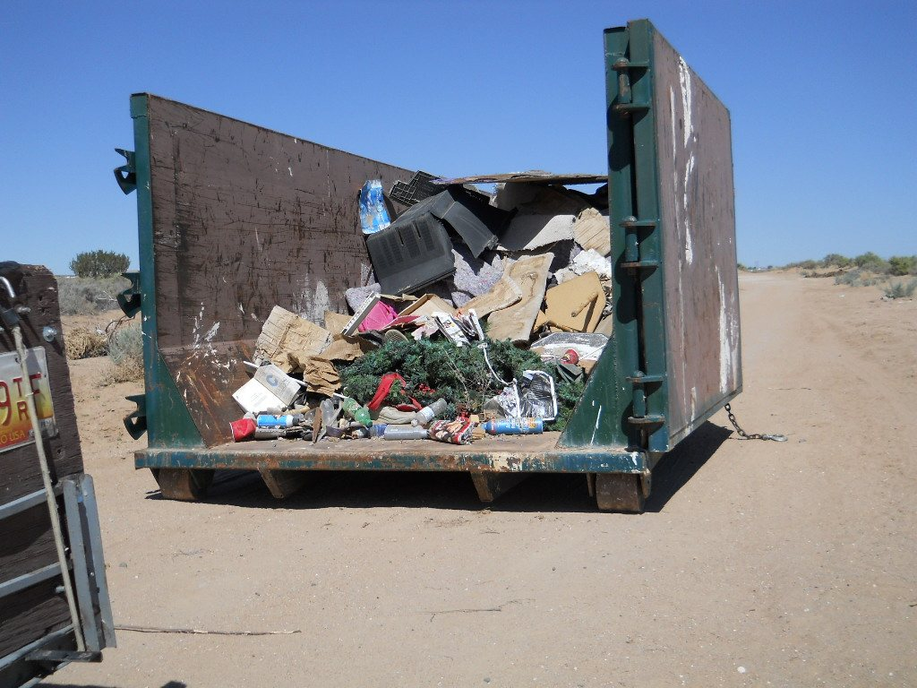 Photo of dumpster and illegal dumping inside